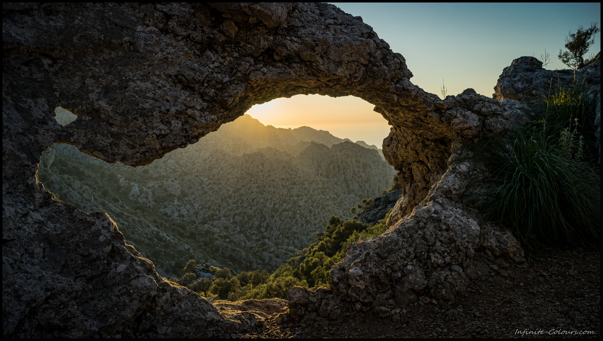 View through the natural arch on the S'Entreforc karst mountains, Torrent de Pareis at sunset